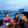 Group shot of three friends dining with a sky view atop LeVeL33