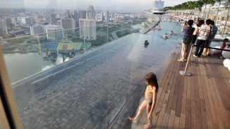 A day shot of people swimming in the Sands SkyPark pool and visitors taking photos