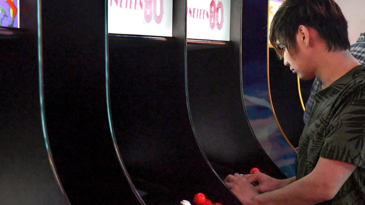 Xian in front of an arcade machine
