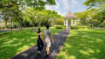 Couple strolling along a footpath at the Singapore Botanic Gardens