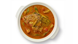A plate of fish head curry cooked with vegetables and fish head