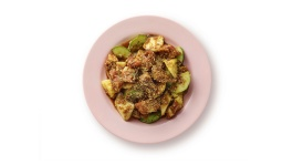 A rojak dish with peanuts, dough fritters, fruits and sticky dark sauce