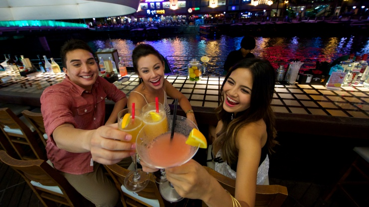 3 friends enjoying drinks at Clarke Quay